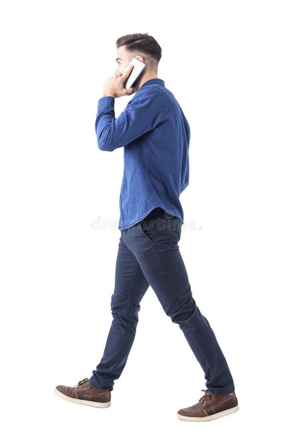 Conversa vestida formal adulta nova do homem no telefone que anda e que olha afastado Vista lateral imagens de stock
