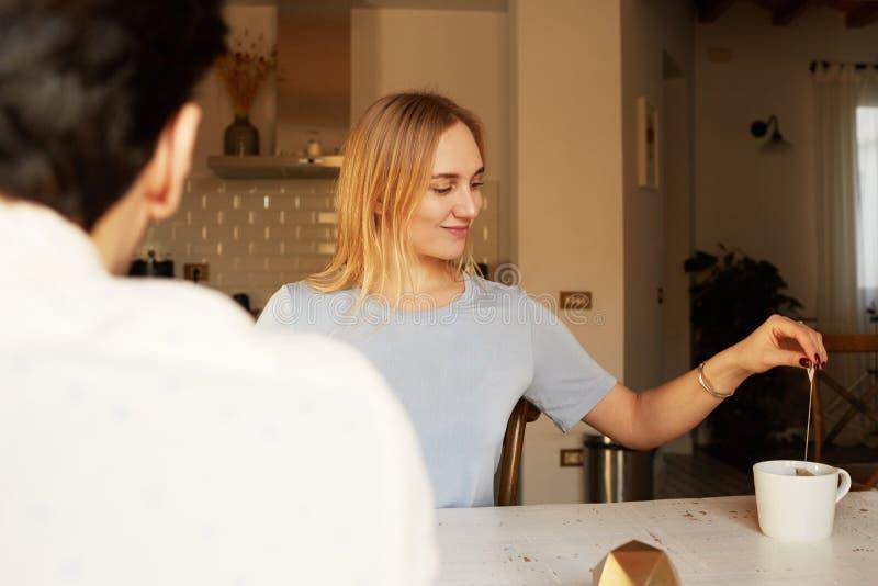Conversación del hombre confiado y de la mujer rubia joven en casa imágenes de archivo libres de regalías