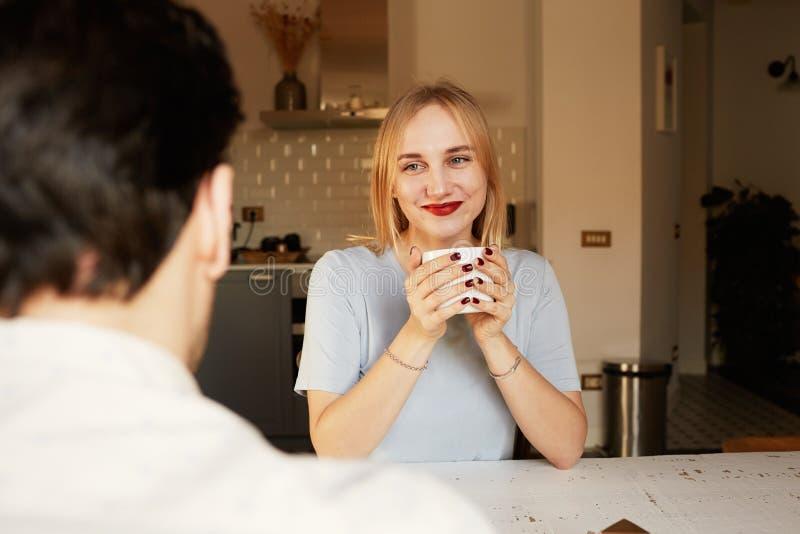 Conversación del hombre confiado y de la mujer rubia joven en casa imagen de archivo libre de regalías