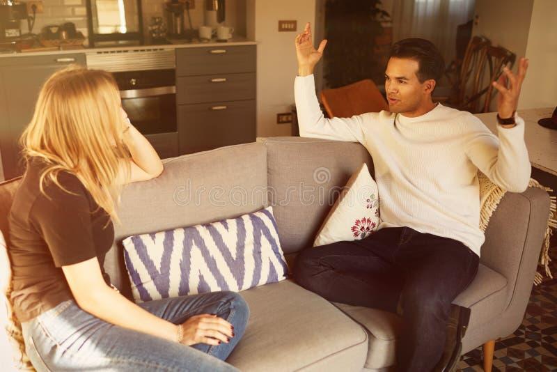 Conversación sobre el sofá del hombre confiado y del apartamento rubio joven de la mujer en casa fotografía de archivo libre de regalías