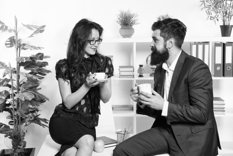Conversaci?n agradable del hombre y de la mujer durante descanso para tomar caf? Discusi?n de rumores de la oficina Pida recomend foto de archivo