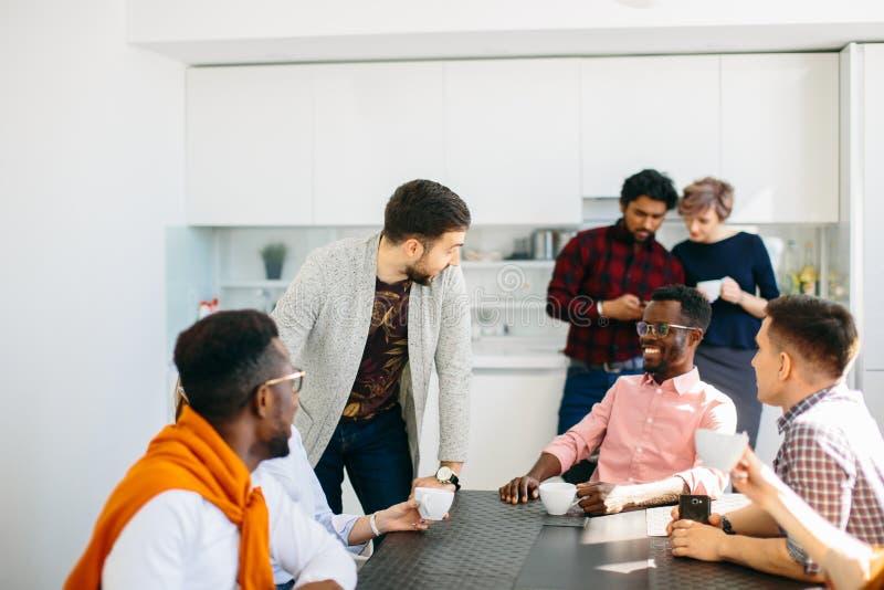 Conversation amicale parmi des employés de bureau au-dessus d'une tasse de thé image libre de droits