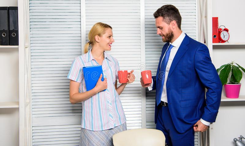 Conversation between colleagues. Boss and worker discuss working plan. Relations at workplace. Colleagues spend time. Coffee break. Friendship and personal royalty free stock photo