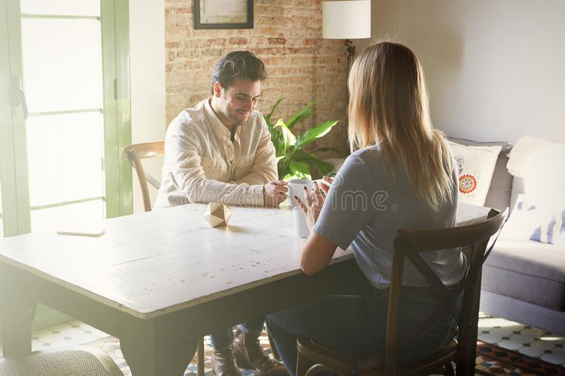 Conversation of confident man and young blond woman at home royalty free stock photo