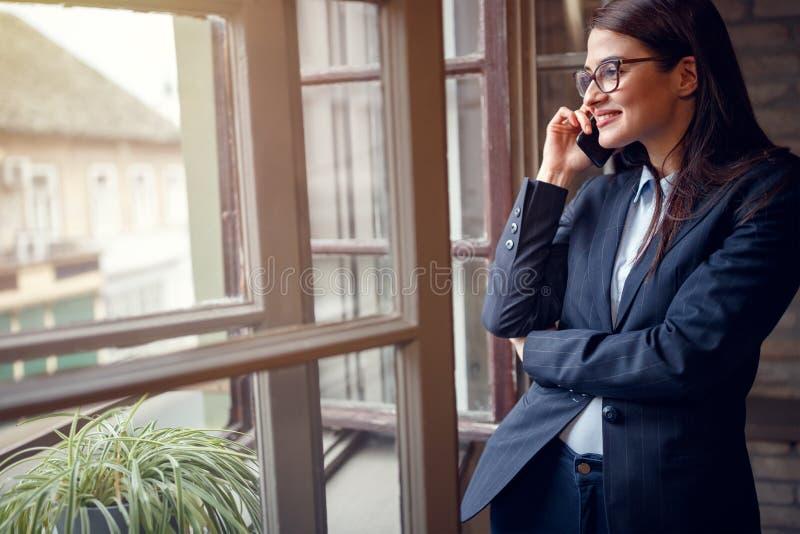 Conversation d'affaires au téléphone portable par la fenêtre image libre de droits