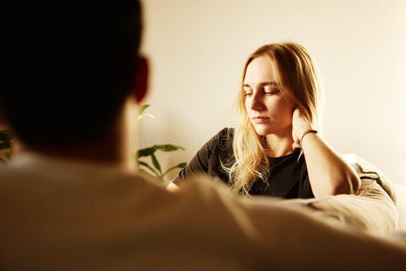 Conversation d'homme attirant et de jeune femme blonde à la maison Famille à la maison photos stock