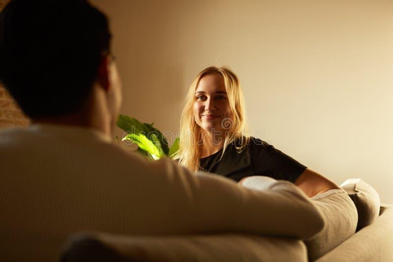 Conversation d'homme attirant et de jeune femme blonde à la maison Famille à la maison images libres de droits