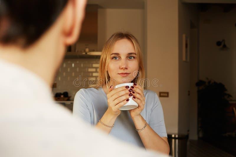 Conversation d'homme sûr et de jeune femme blonde à la maison photo stock
