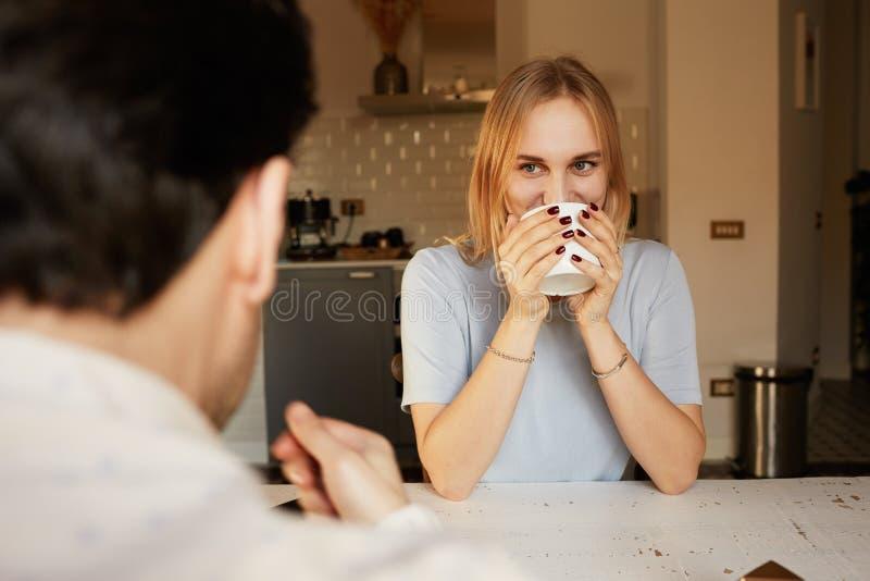 Conversation d'homme sûr et de jeune femme blonde à la maison photographie stock libre de droits