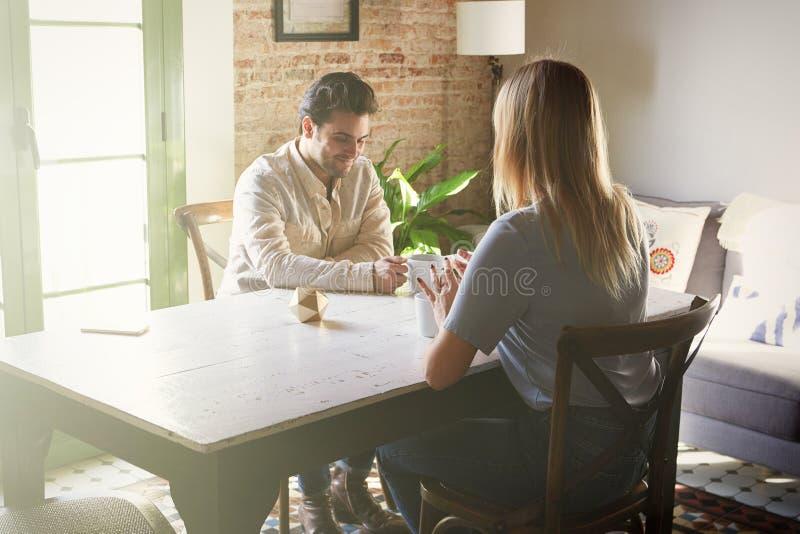 Conversation d'homme sûr et de jeune femme blonde à la maison photo libre de droits