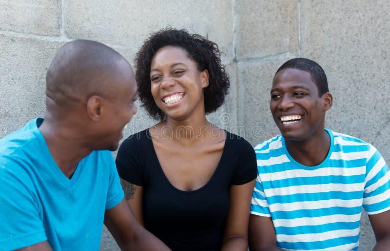 Conversation de trois hommes africains et de femme photo stock