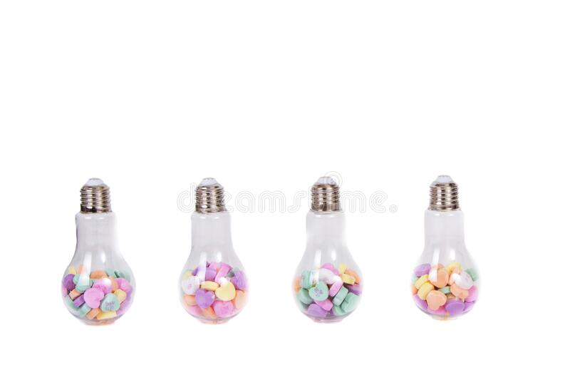 Conversation hearts in a light bulb container. Isolated on white royalty free stock images
