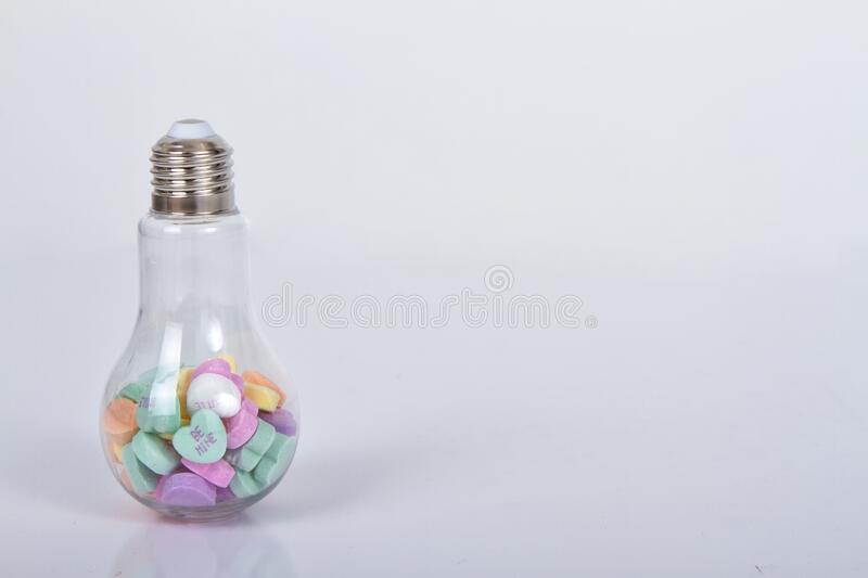 Conversation hearts in a light bulb container. On white background stock image