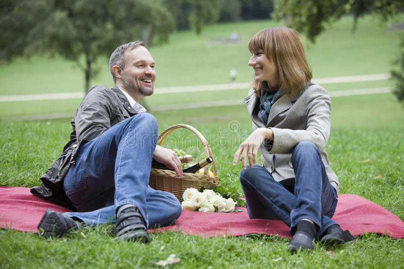 Conversation by picnic. Romantic couple by picnic in a city park stock image