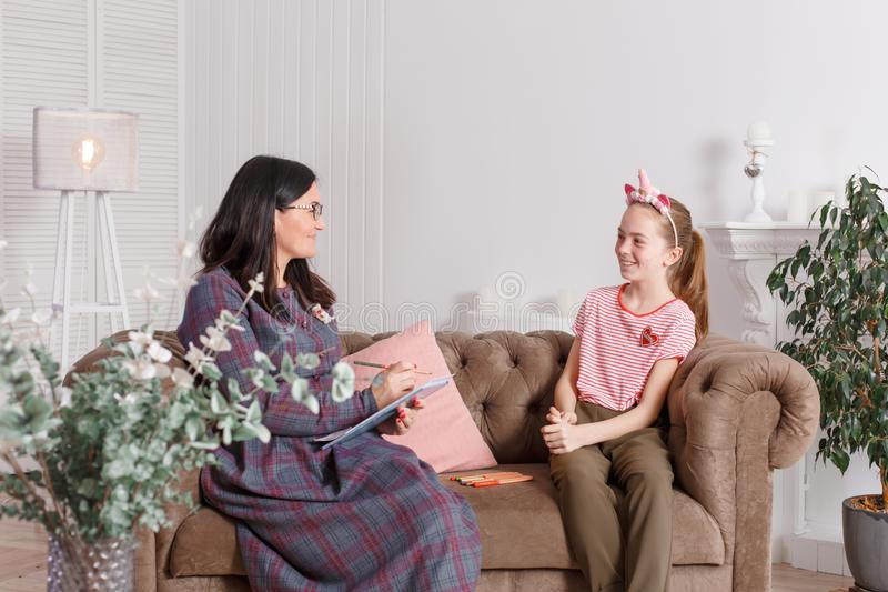 Conversation of a professional psychologist with a teenage girl. They sit on the couch and draw. The method of work of a child. Psychotherapist royalty free stock image