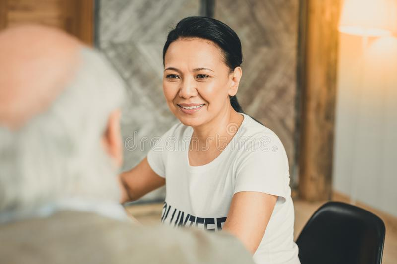 Smiling dark-haired woman gently looking on old man. Conversation with retiree. Smiling dark-haired women gently looking on old men while working as professional royalty free stock images