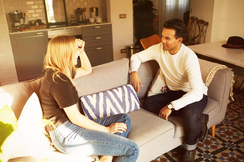 Conversation on sofa of confident man and young blond woman at home apartment stock photos