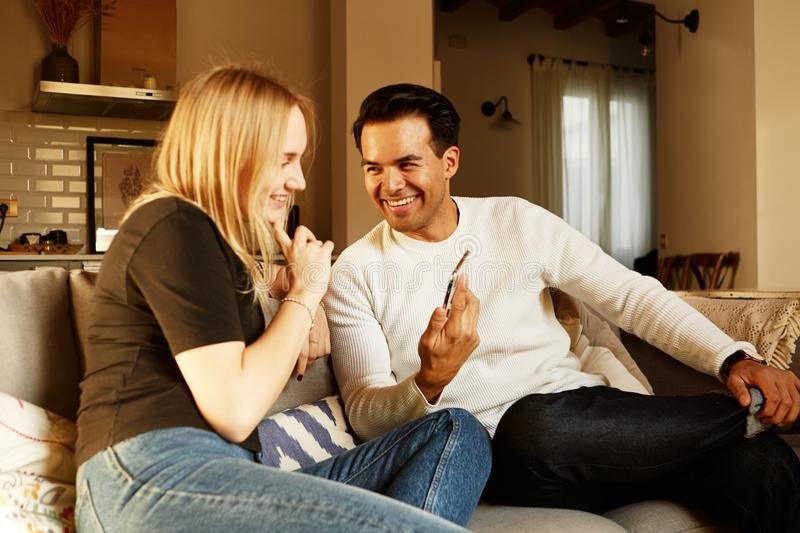 Conversation on sofa of young family couple at home apartment stock photography