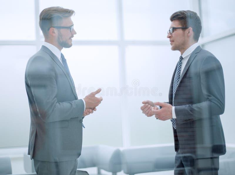 Conversazione dei soci commerciali nell'ufficio immagini stock libere da diritti