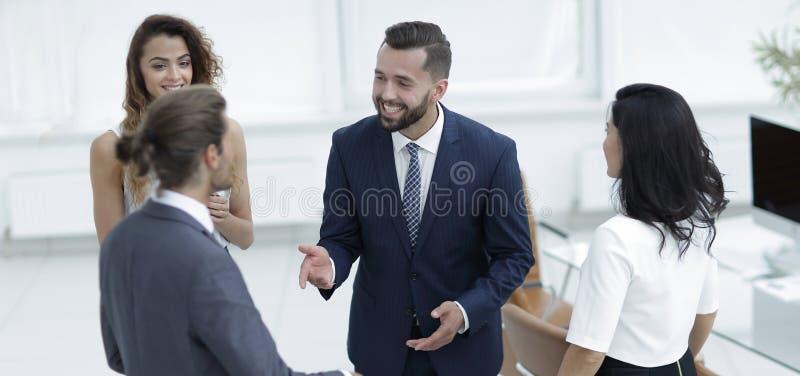Conversazione del gruppo di affari, stante nell'ufficio fotografia stock