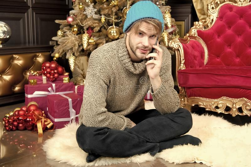 Conversazione del tipo sul telefono cellulare all'albero di Natale immagine stock