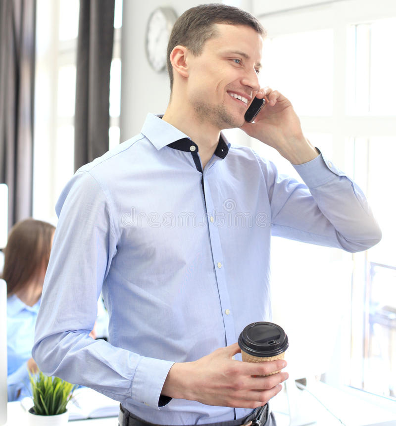 Conversazione dell'uomo d'affari al cellulare e sguardo dalla finestra fotografie stock