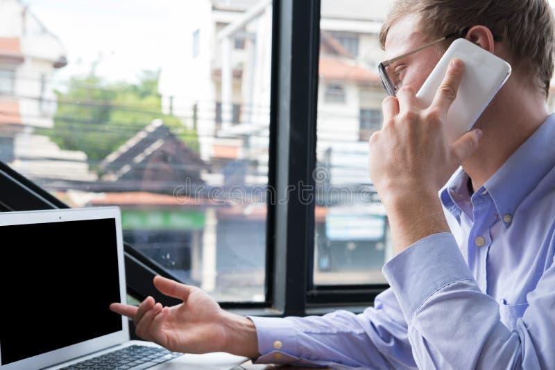 Conversazione dell'uomo d'affari sul telefono cellulare all'ufficio chiamata del giovane su MP fotografie stock libere da diritti