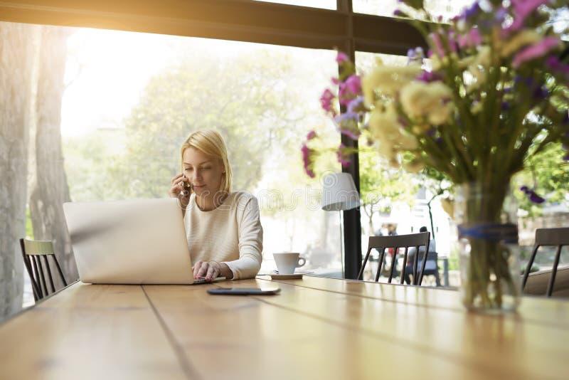Conversazione della persona femminile sullo smartphone mentre guardando lo schermo del NET-libro fotografia stock libera da diritti