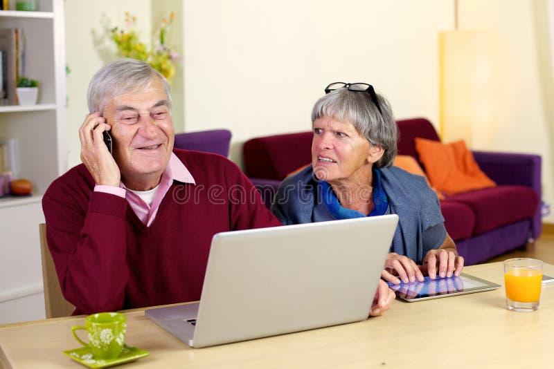 Conversazione di prima generazione felice sul telefono con il figlio a casa fotografia stock