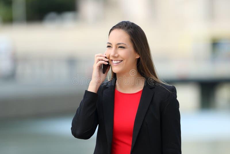 Conversazione esecutiva sorridente sul telefono nella via fotografie stock