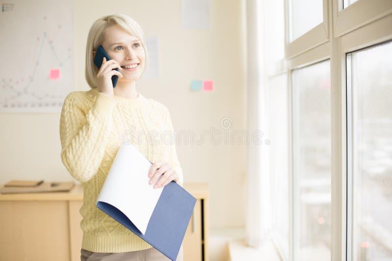 Conversazione femminile sul telefono cellulare in ufficio immagine stock libera da diritti
