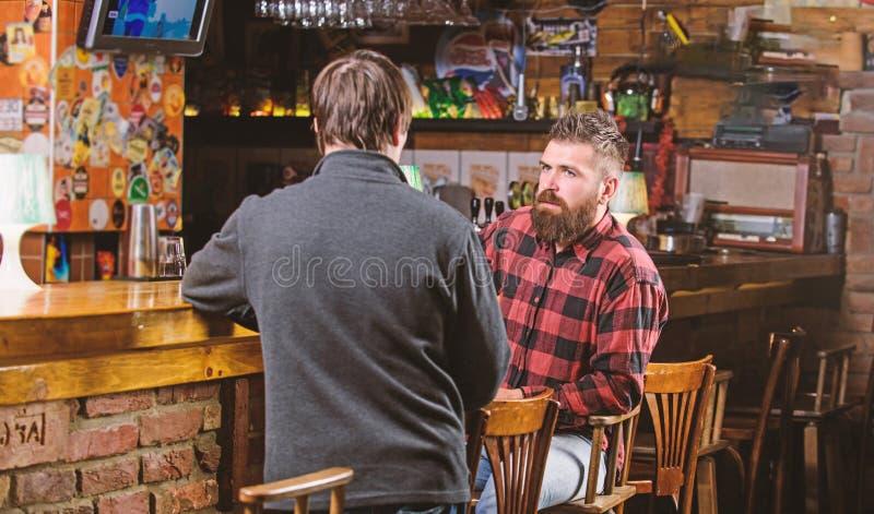 Conversazione interessante Uomo barbuto brutale dei pantaloni a vita bassa spendere svago con l'amico al contatore della barra Uo fotografia stock libera da diritti