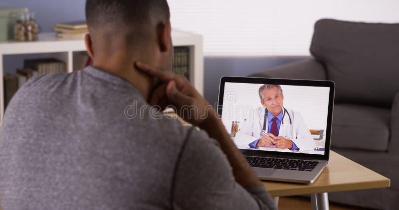 Conversazione paziente nera con medico senior sul computer portatile immagini stock