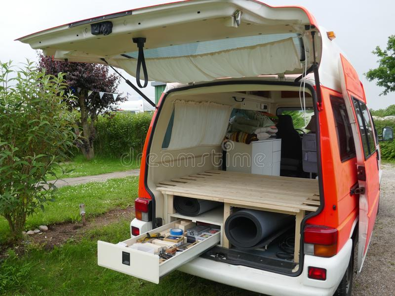 Conversion of a disused ambulance to the motorhome. Installation of a pedestal with storage space, drawers and slatted frame for a royalty free stock photos