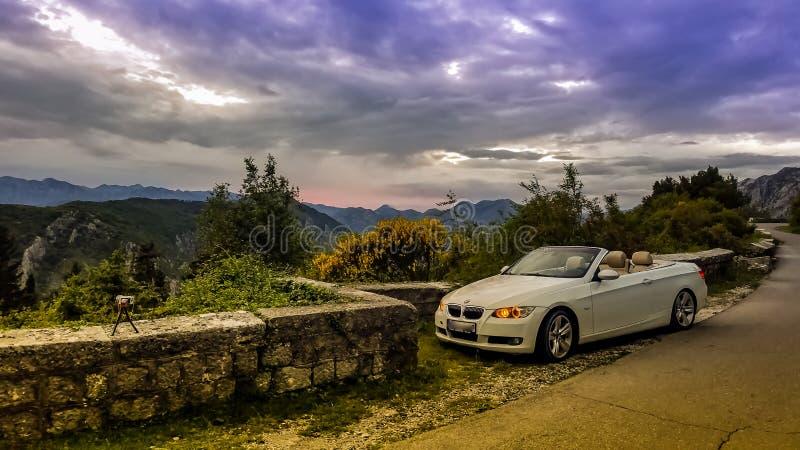 Convertible blanc de luxe sur le fond du ciel de coucher du soleil dans les montagnes image libre de droits