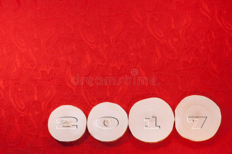 Convex date 2017 on four alder saw cuts on red ornate ethnical f. Abric background. Suitable for christmas and New Year's background royalty free stock photo