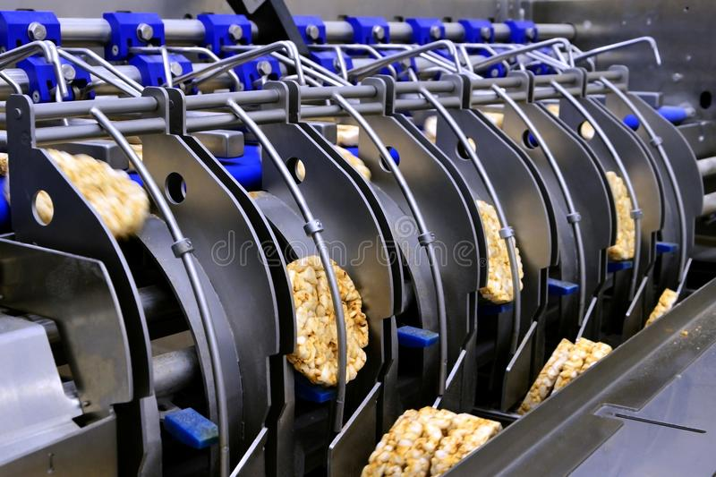Conveyor automatic tape for the production of useful whole-grain extruder crispbread stock image