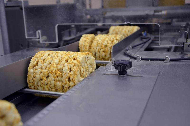 Conveyor automatic tape for the production of useful whole-grain extruder crispbread. packing organic multi-barley briquetted. Crispbread on factory stock photo