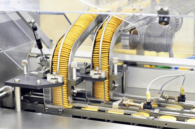 Conveyor belt with biscuits in a food factory - machinery equipm royalty free stock images