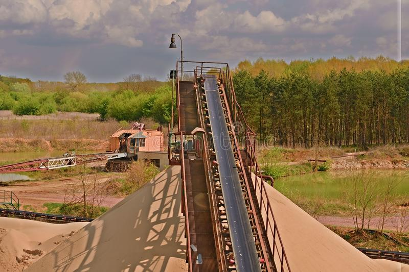 Conveyor belts and sand heaps. Construction industry. Sand quarry, heavy duty machinery. Horizontal photo. Strong HDR effect stock image
