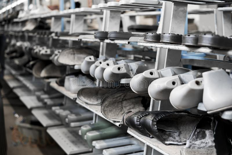 The conveyor on a shoes factory with shoe and sole. Mass production of footwear. stock image