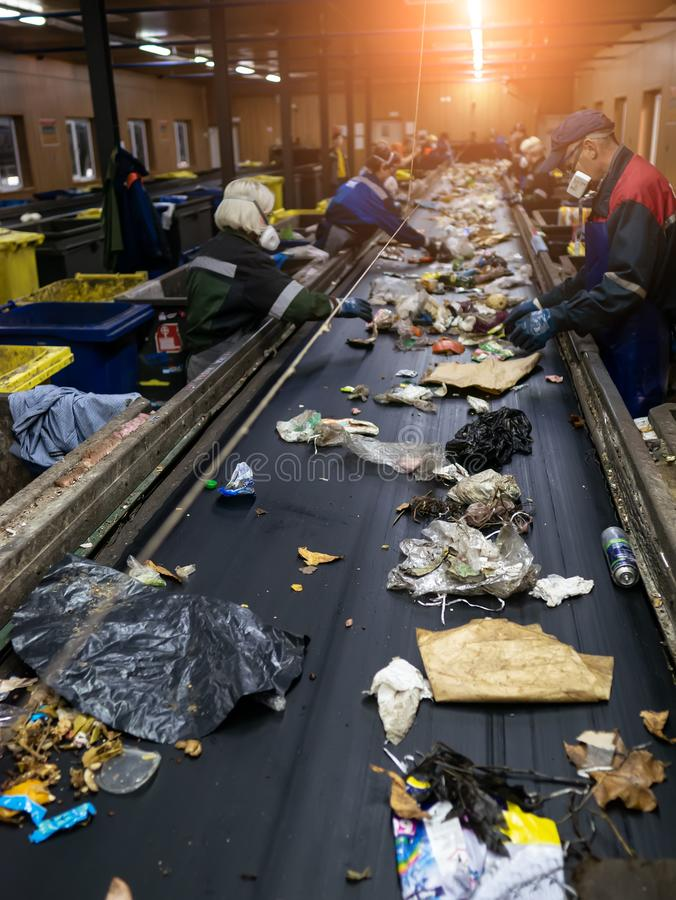 Conveyor for sorting garbage waste by people. Garbage processing royalty free stock images
