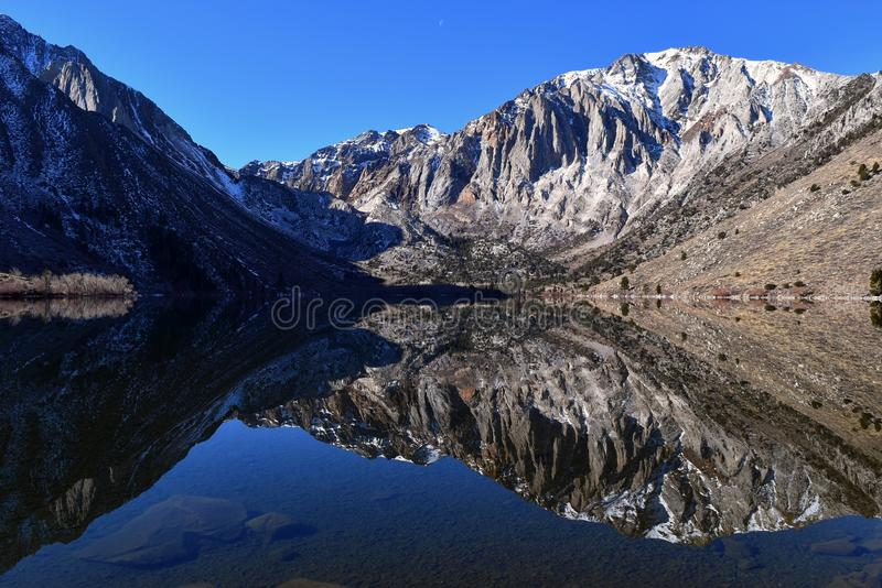 Convict Lake, Inyo. Reflection in a still Convict Lake with afternoon moon, east Sierras, Inyo NF, California, March 2018 royalty free stock images
