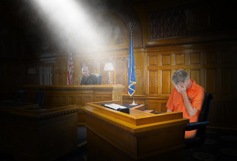 Law, Justice, Crime, Punishment, Judge, Convict, Prisoner. A convict prisoner stand trial for a crime and faces punishment from a legal law judge in a court room royalty free stock photo