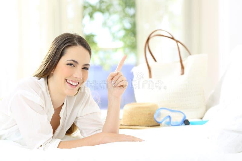 Convidado do hotel que aponta acima em uma cama em férias de verão imagem de stock