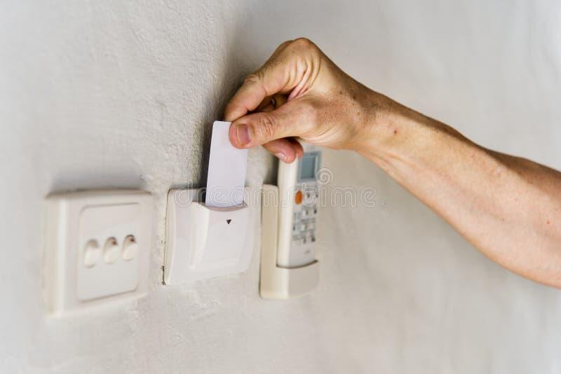 Convidado do hotel que introduz o keycard para girar sobre a eletricidade foto de stock