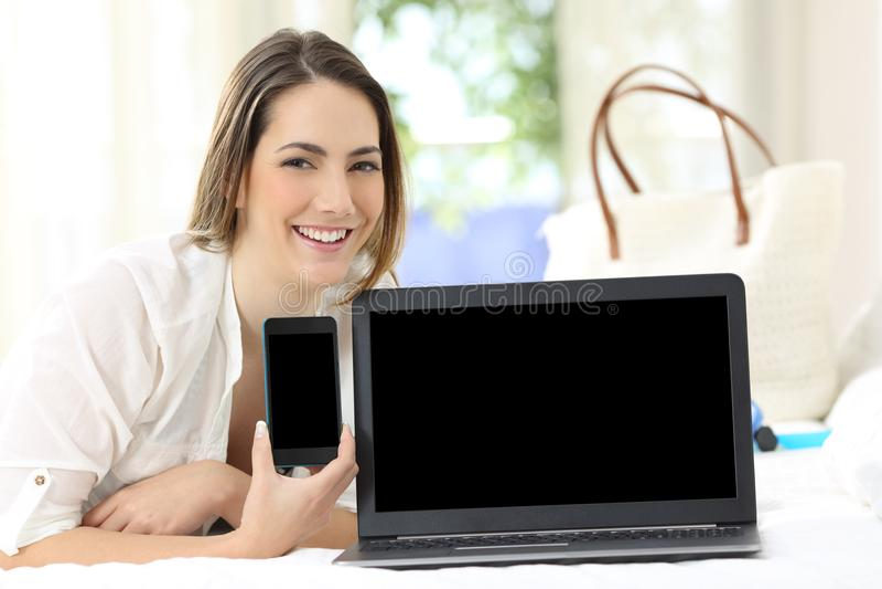Convidado do hotel que mostra telas vazias do smartphone e do portátil fotografia de stock royalty free