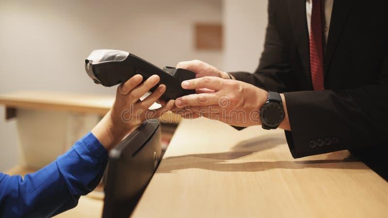 Convidado do hotel que paga a viagem de negócios com cartão de crédito e posição fotos de stock