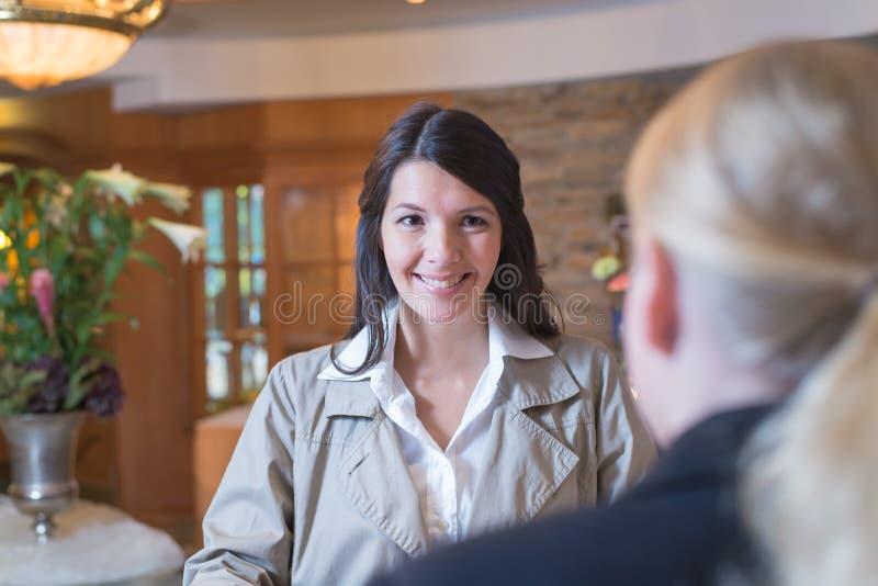Convidado fêmea de sorriso em uma entrada do hotel fotografia de stock