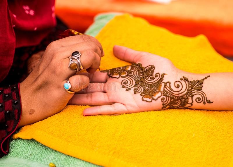 Convidado indiano do casamento que tem o mehndi aplicado à palma da mão Arte tradicional da hena imagem de stock